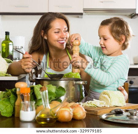 Positive young mother with little daughter cooking at home kitchen