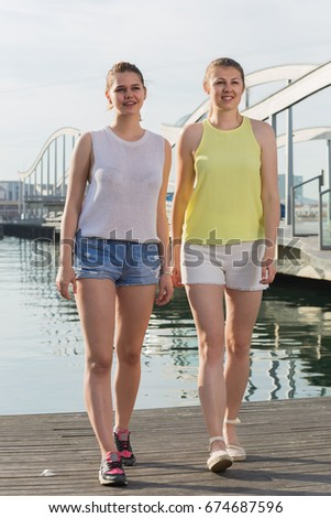 positive young russian girls standing on berthand and smiling
