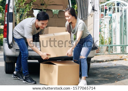 Positive young Vietnamese couple taking heavy cardboard boxes out of truck #1577065714