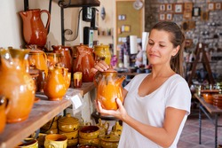 Positive young woman choosing handmade earthenware in pottery shop