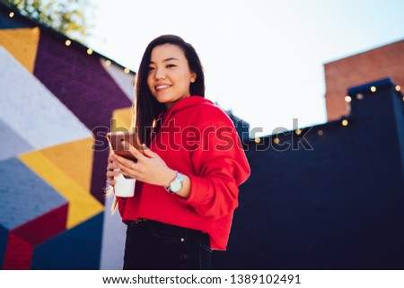 Positive young woman dressed in casual wear installing app on mobile phone while smiling at camera, portrait of hipster girl holding smartphone device standing in outdoors and using public 4G internet