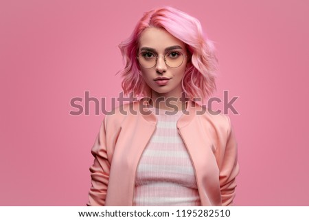 Positive young woman in stylish glasses looking at camera while standing on pink background