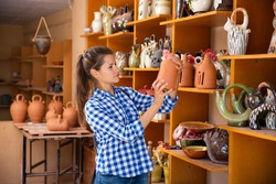 Positive young woman looking for handmade ceramic products in craft pottery shop