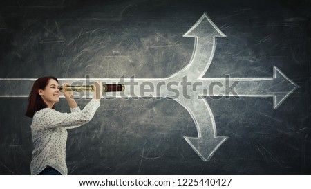 Positive, young woman looking through a spyglass in front of a blackboard as a crossroad arrows splitted in three different ways. Choosing between up, down and ahead. Difficult decision concept. #1225440427