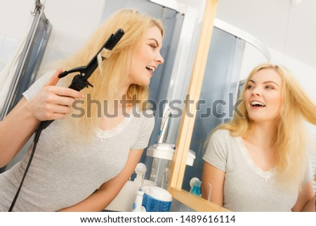 Positive young woman preparing her blonde hair, using curling pin in home bathroom. Hairdo curler creating hairstyle.