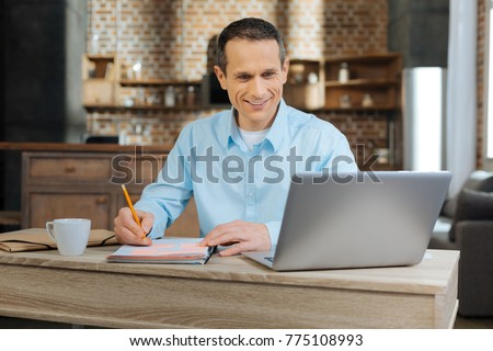 Positivity at work. Cheerful businessman keeping smile on his face and turning head to laptop while writing notices #775108993