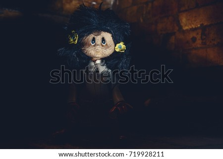 Possessed rag doll emerge form darkness of sewer. Terror scene. Original photo of ancient toy (copyright free) retouched and colored, neither artworks, layers nor external references were used