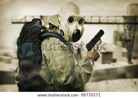 Post apocalypses world halloween concept. Portrait of man in gas mask with handgun