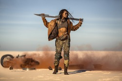 Post-apocalyptic biker woman with weapon outdoors. Young slim girl warrior in shabby clothes holding sword standing in a confident pose against the broken burning motorcycle looking away. Nuclear post