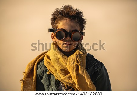Post-apocalyptic boy outdoors in the desert. Nuclear post-apocalypse. Life after doomsday concept. Desert and dead wasteland on the background.