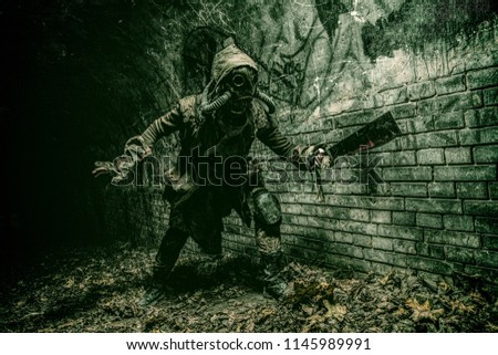 Post apocalyptic mutant creature or survivor in tatters and gas mask jumps out of darkness and attacking with handmade machete in abandoned tunnel, frightening dungeon or city old sewage collector