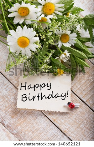 Post card with wild flowers and card with words Happy Birthday on it.