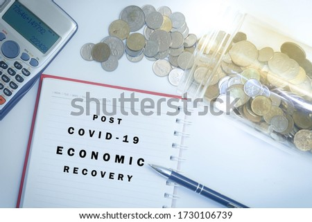 Post covid-19 economic recovery conceptual. Top view of an image with 'POST COVID-19 ECONOMIC RECOVERY' text on the book with calculator, coins spilling out of from jar and pen. Stock photo ©