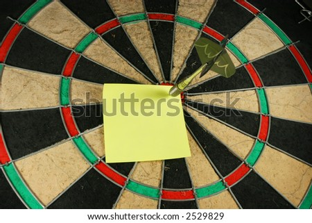 Post-It note on a dart board. Dart used as a push pin.