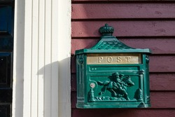 Post office box made of green metal hanging on a red wooden exterior house wall with white trim. The letterbox has a lock and the word post on it. There's a horse on the little door of the mailbox.