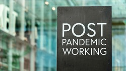 Post Pandemic Working sign in front of a modern office building