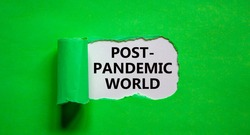 Post-pandemic world symbol. The words 'Post-pandemic world' appearing behind torn green paper. Beautiful green background, copy space. Medical and COVID-19 pandemic post-pandemic world concept.