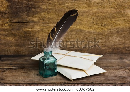 Postage on the background of an old wooden board with a pen for writing in the ink