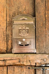 Postal mailbox in a golden color on an old door from massive wood.