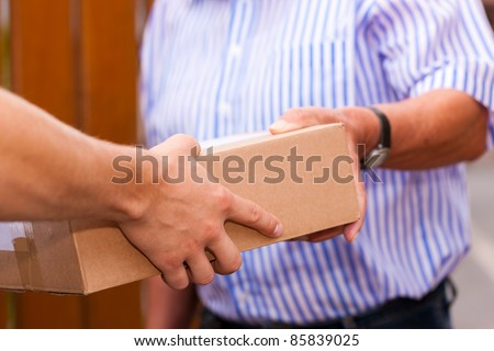 Postal service - delivery of a package; the postman is giving the package to the customer (only hands and package to be seen) - stock photo