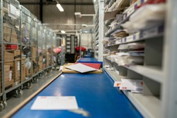 Postal service, post office inside. Letters on a sorting frame, table and shelves in a mail delivery sorting centre.