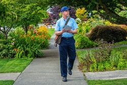 Postal worker hand delivering mail while walking down a sidewalk in a upscale neighborhood