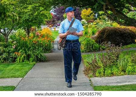 Postal worker hand delivering mail while walking down a sidewalk in a upscale neighborhood Stockfoto ©