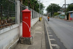 Postbox on footpath beside street in Thailand. Motorbike running, wall and house background. Concept of communication, letter, vintage, sidewalk, perspective.