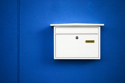 Postbox white on a blue wall ,outdoor