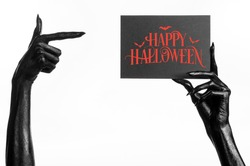 Postcard and Happy Halloween theme: black hand of death holding a paper card with the words Happy Halloween on a white isolated background in studio