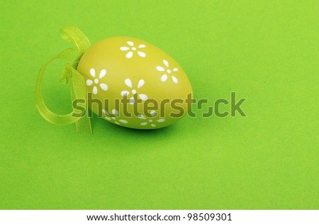 postcard as a green with small lovely white flowers painted egg on green background on Easter/painted egg