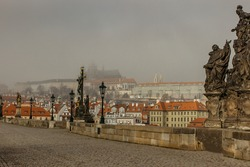 Postcard view of Prague Castle in mist from Charles Bridge,Czech republic.Famous tourist destination.Prague panorama.Foggy morning in city.Amazing European cityscape cold weather.Romantic atmosphere