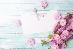 Postcard with empty tag for your text and fresh pink flowers on turquoise painted wooden planks in ray of light . Selective focus is on tag.