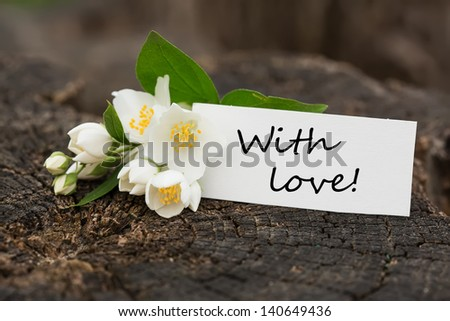 Postcard with fresh flowers and tag with words with love