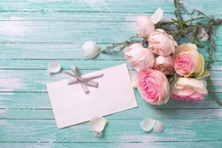 Postcard with fresh roses flowers and empty tag for your text on turquoise painted wooden background. Selective focus.