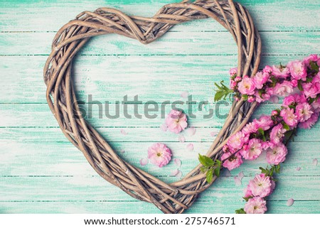 Postcard with  heart and pink flowers  on turquoise wooden  background. Selective focus. Toned image.