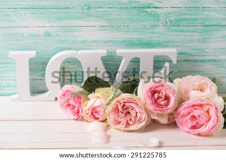 Postcard with sweet pink roses flowers and word love on white painted wooden background against turquoise wall. Selective focus. Place for text.