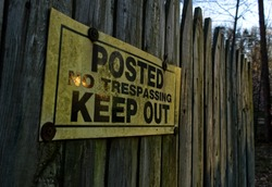 Posted No Trespassing Keep Out Sign on a Old Fence in the Evening