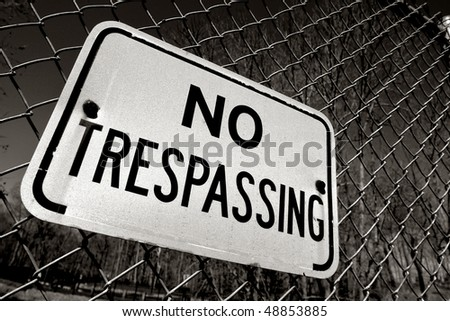 Posted no trespassing warning sign on chain link wire fence