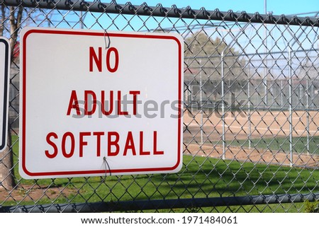 Posted red and white sign at a youth sports complex. No adult softball. Men's, women's and coed softball leagues promote fitness and community through this active team sport.                       Foto stock ©