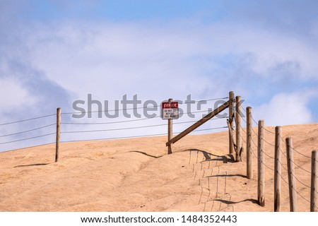 """Posted sign on a edge of a cliff of Cape Kiwanda read """"Danger"""" and """"Do not go beyond this point"""".  A barrier protecting people from going into a dangerous places #1484352443"""