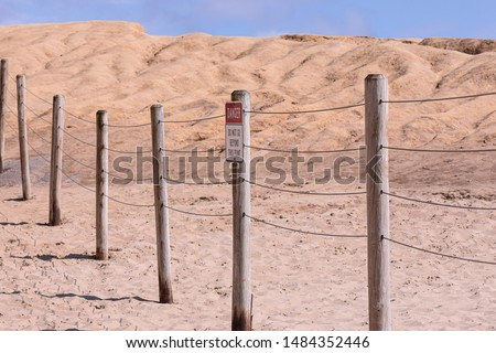"""Posted sign on a wire fence read """"Danger"""" and """"Do not go beyond this point"""". A protective barrier around dangerous place #1484352446"""