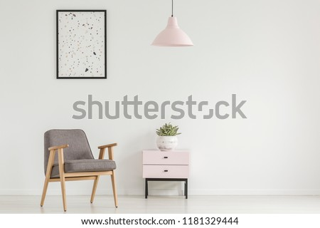 Poster above grey wooden armchair next to cabinet with plant in white flat interior with lamp. Real photo #1181329444