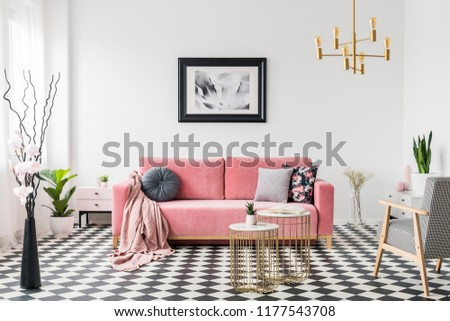 Poster above pink sofa in spacious living room interior with patterned armchair and plants. Real photo #1177543708
