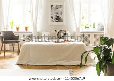 Poster above white bed in bedroom interior with grey armchair and drapes at windows. Real photo