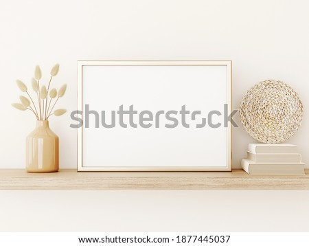 Poster art mockup with horizontal gold metal frame, dried grass in vase, basket plate and books on empty warm beige wall background. Boho interior decoration. A4, A3 format. 3d rendering, illustration
