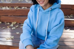 poster close up details of oversized blue color hoodie  at female.fashion and wear concept. warm oversize wear at woman.space for text and logo.close up details of oversize wear.mock up lips,hair