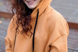 poster close up details of oversized orange color hoodie at female.fashion and wear concept. warm oversize wear at woman.space for text and logo.close up details of oversize wear.close up lips.sweater