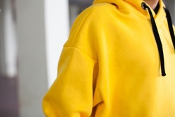 poster close up details of oversized yellow color hoodie  at male.fashion and wear concept. warm oversize wear at man.space for text and logo.close up details of oversize wear.horizontal banner wear