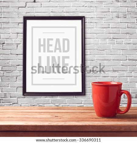 Poster mock up template with red cup on wooden table over brick white wall